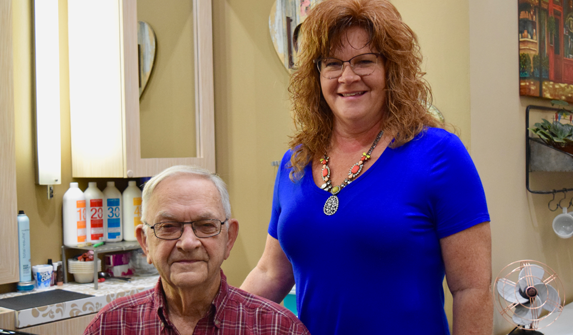 Photo of Sandra and her father in her salon.