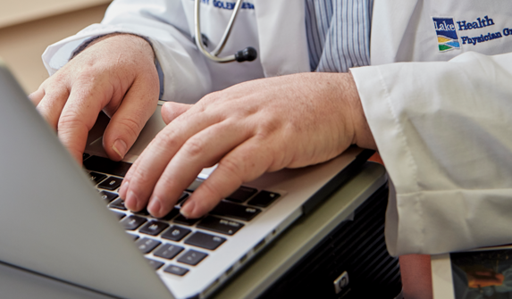 Close up image of physician hands typing on a computer